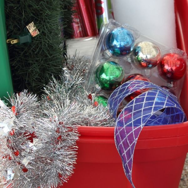 overflowing red tote of Christmas decorations