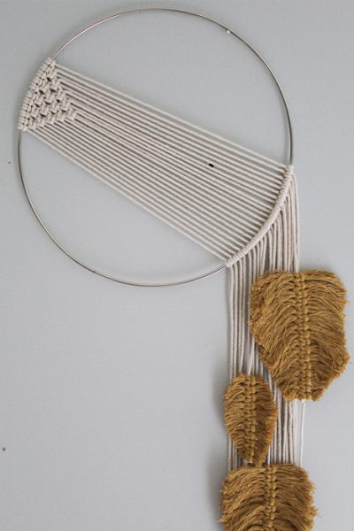Simple macrame wall hanging with feathers in a mustard color hanging from strings hangin down the right size of the silver hoop