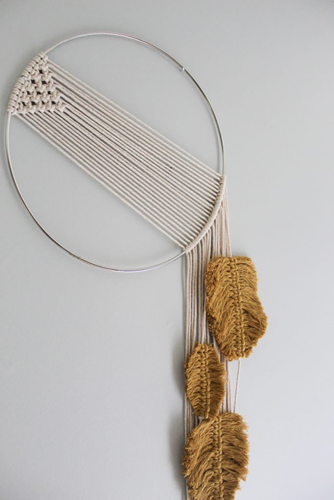 Macrame wall hanging with feathers hanging on the wall.