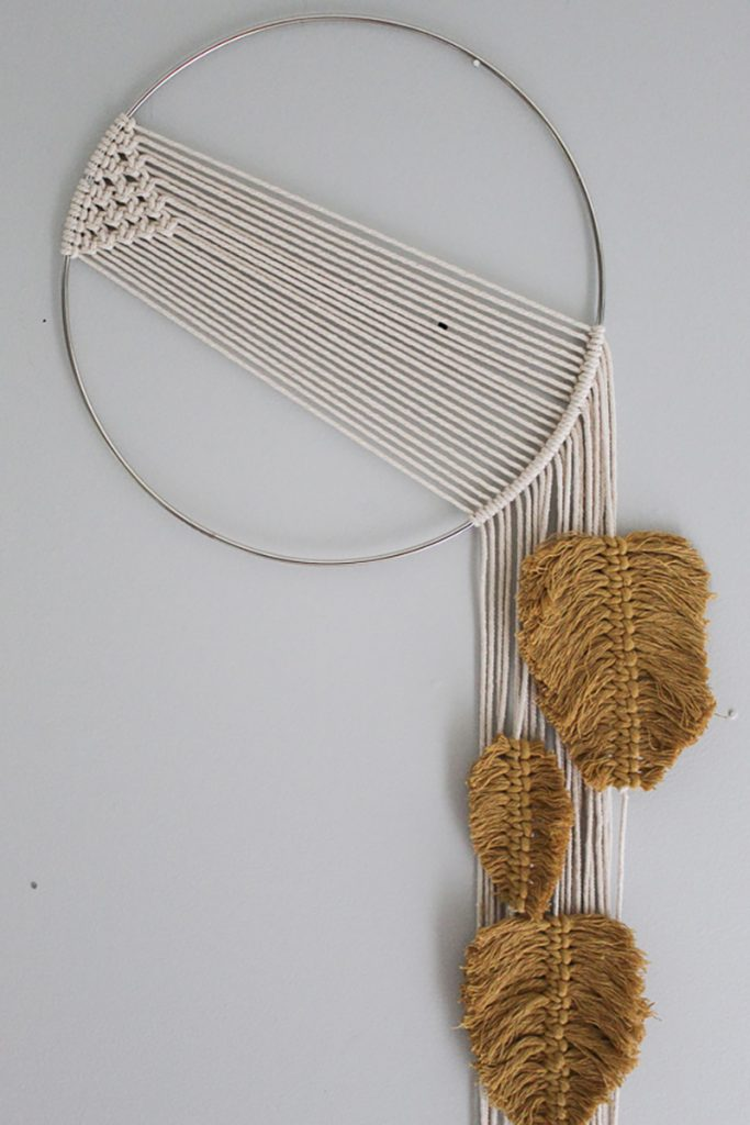 Simple macrame wall hanging with feathers in a mustard color hanging from strings hanging down the right size of the silver hoop