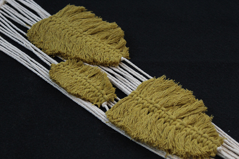 3 feathers made of mustard colored macrame string
