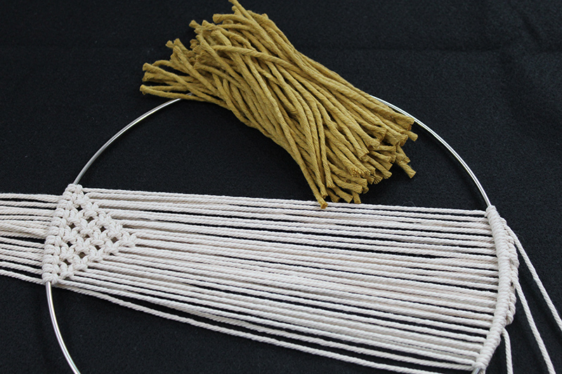 pile of mustard strings laying on black background next to simple macrame wall hanging