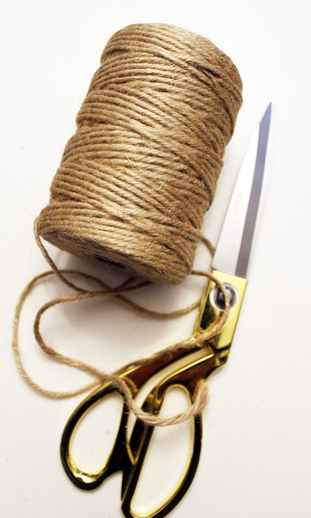 roll of jute rope and a pair of gold handled scissors