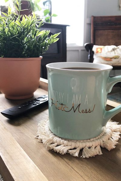 coffee cup sitting on a macrame coaster