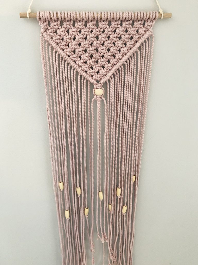 Completed pink simple macrame wall hanging with beads