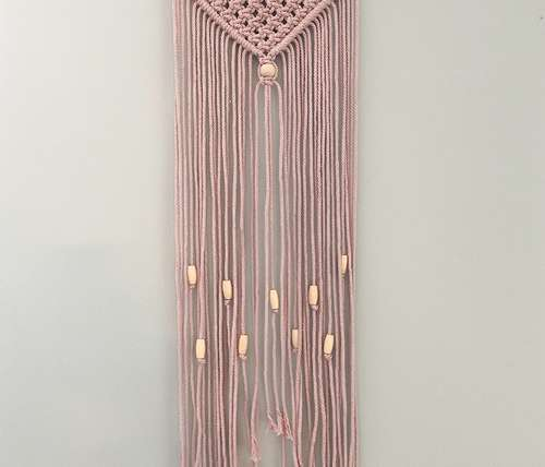 simple macrame wall hanging with beads made with dusty pink macrame string and natural colored beads