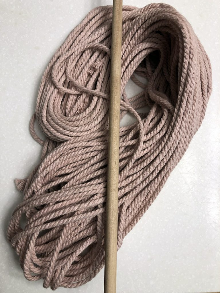 pink macrame string with wooden dowel rod laying on top