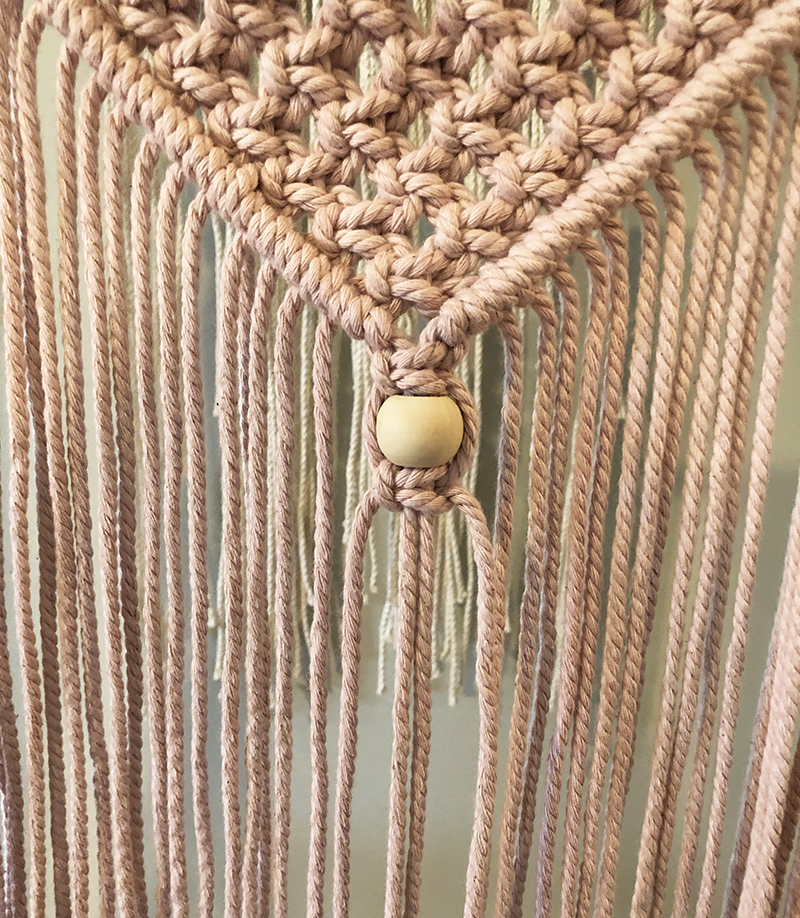 pink macrame wall hanging made using square knots with a round bead.
