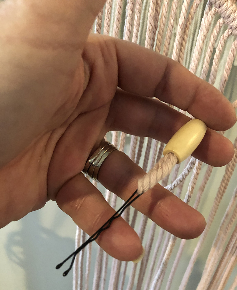 threading an oval bead onto the string using a bobby pin
