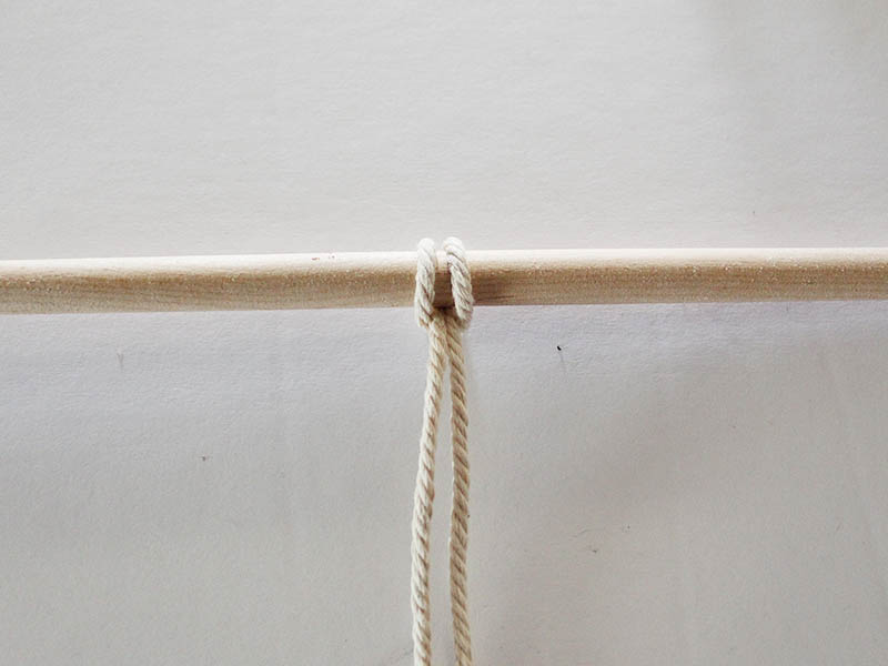 natural colored macrame rope tied to a dowel using a reverse lark's head knot