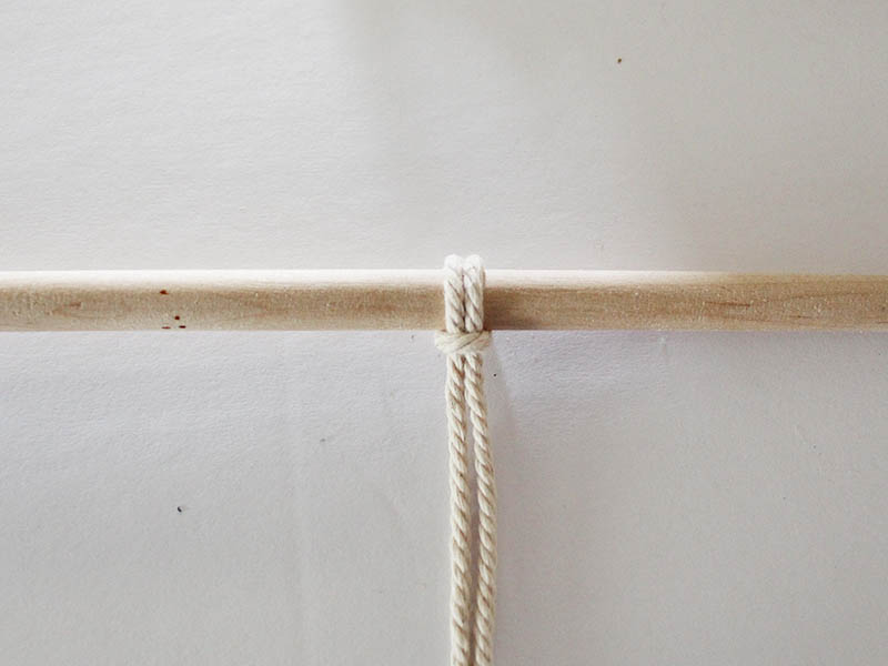 macrame rope tied in a lark's head knot to a dowel rod