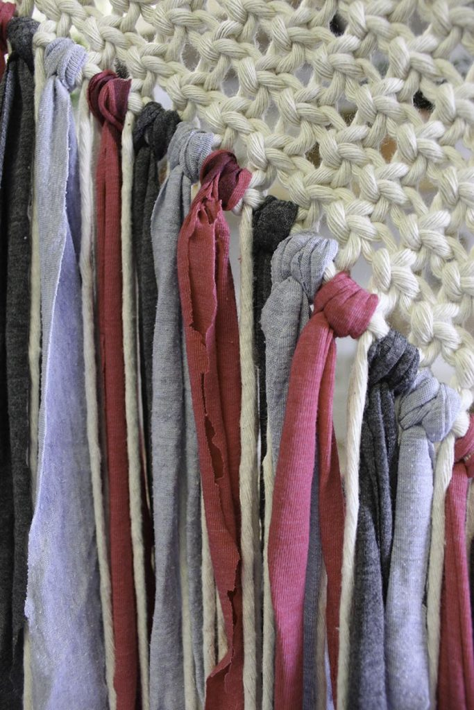 t-shirt strips in pink, charcoal and denim blue tied to the square knot pattern on the macrame wall hanging