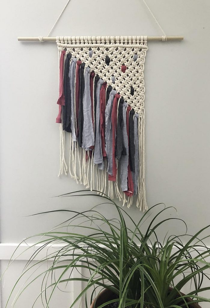 Macrame wall hanging tied with square knots in a triangle pattern with pink, charcoal, and denim blue t-shirt fringe