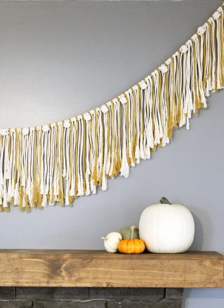Macrame garland hanging above a mantle with a large white pumpkin and small orange and white pumpkin