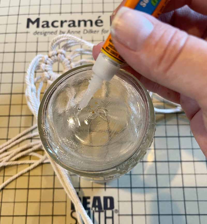 applying super glue to the bottom of a jar