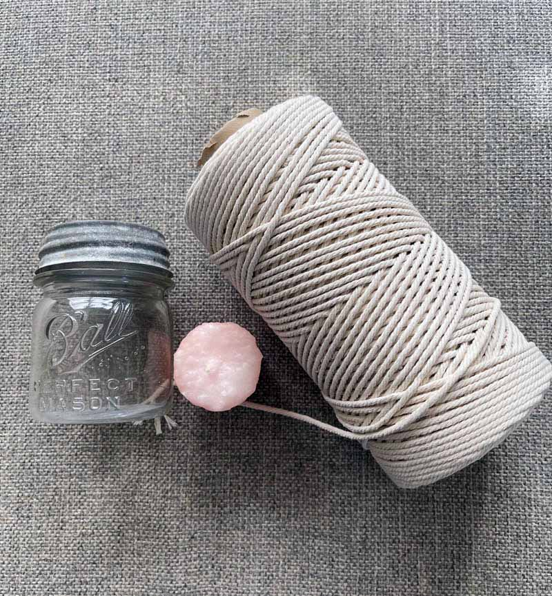 roll of natural macrame string, a small bar jar and an a pink votive candle