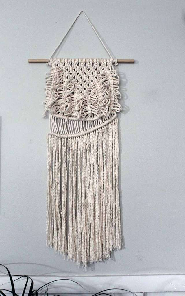 natural colored macrame wall hanging hanging on a wall