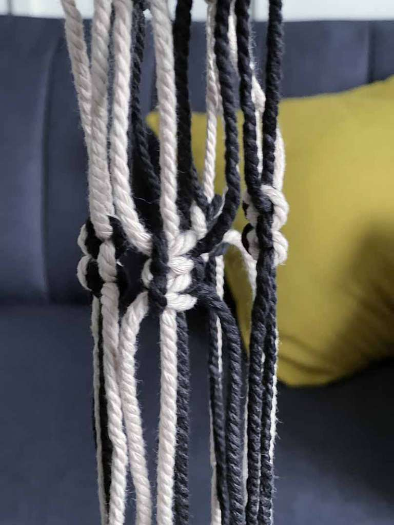 pink and black macrame strings tied together in square knots