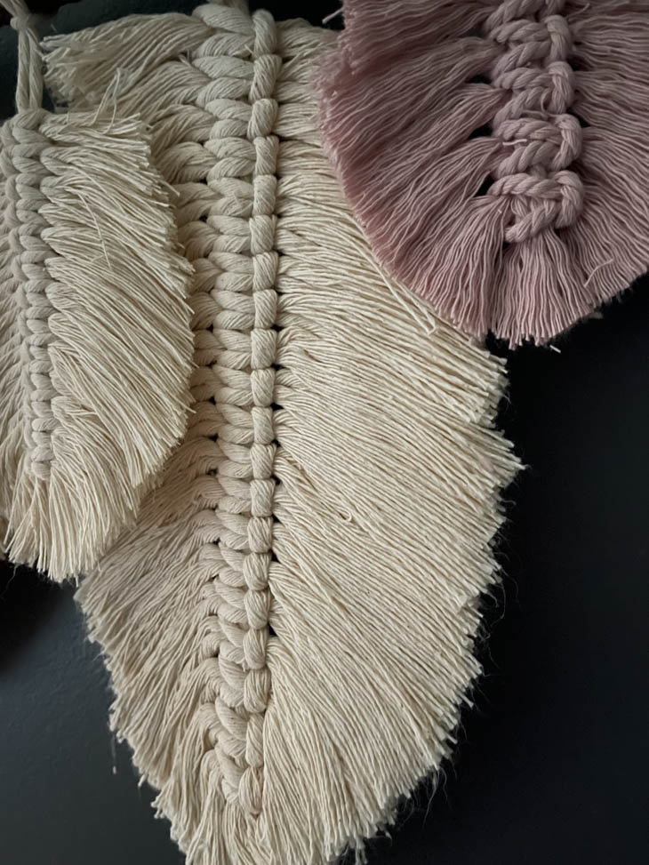 close up of large feather on finished macrame feather wall hanging