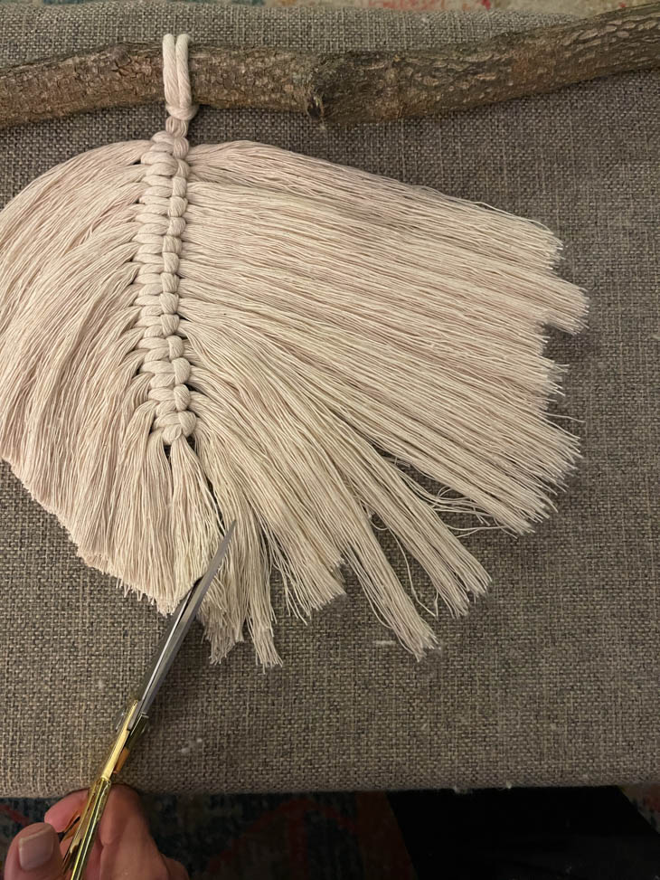 macrame feather being trimmed with scissors