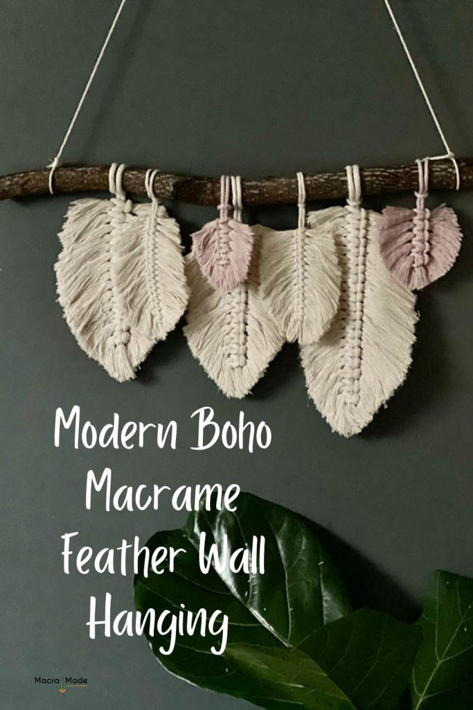 natural and pink macrame feathers hanging on a branch against a dark wall